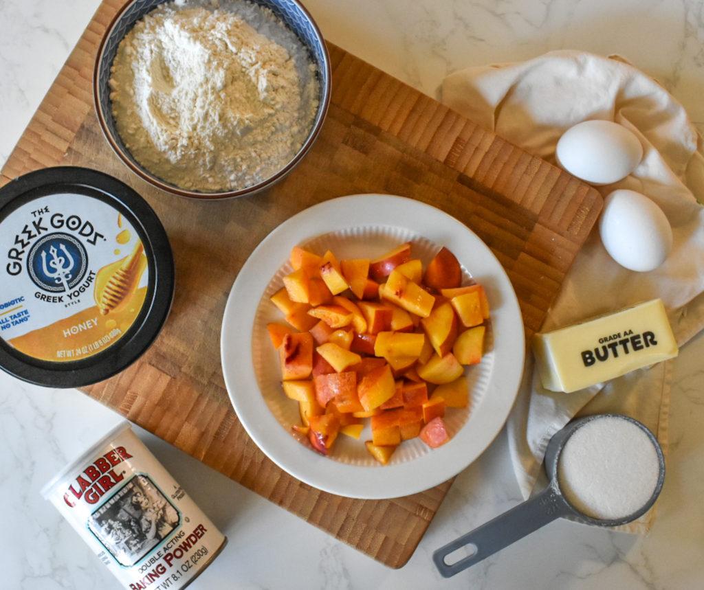 Fresh peaches, eggs, butter, sugar, baking powder, flour and honey yogurt are on a cutting board for this peach dessert recipe.